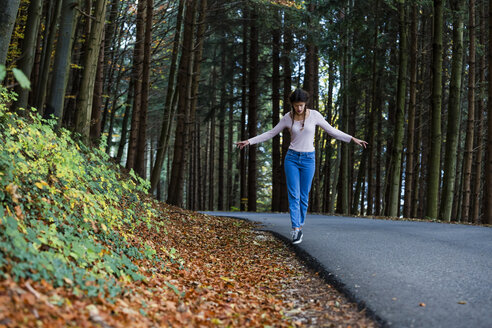 Young woman balancing at roadside in the woods - WVF00823