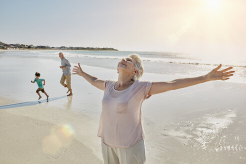 Happy senior woman standing on the beach with arms outstretched - RORF00537