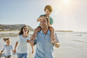 Happy family strolling on the beach - RORF00549