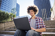 Portrait of young man sitting on stairs using laptop - ABZF01799