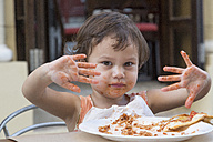 Portrait of little girl eating spaghetti with fingers - DRF01721