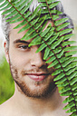 Portrait of smiling young man behind fern leaves - RTBF00616
