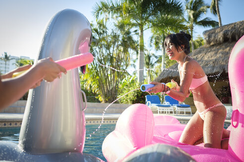 Two women splashing with water guns in swimming pool - ABAF02137