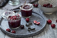 Preserving glasses of cranberry jam and fresh cranberries - YFF00625