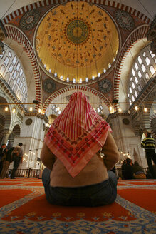 Turkey, Istanbul, back view of woman with headscarf sitting on carpet of Suleymaniye Mosque - DSG01441