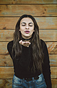 Portrait of young woman with eyes closed blowing a kiss to viewer - RAEF01678