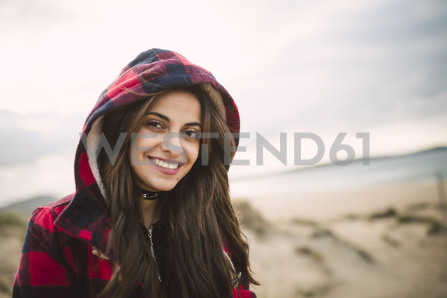 Portrait of smiling young woman wearing hooded jacket on the beach - RAEF01681