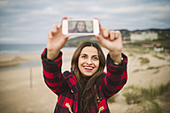 Portrait of smiling woman taking selfie with smartphone on the beach - RAEF01684