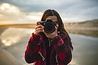 Young woman taking picture with camera on the beach - RAEF01687