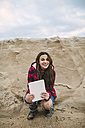 Portrait of smiling young woman with tablet crouching on the beach - RAEF01690