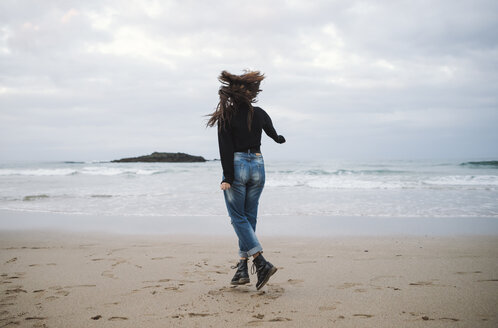 Back view of young woman jumping on the beach - RAEF01699
