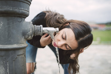 Young woman drinking water from a well - RAEF01705