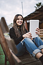 Portrait of smiling young woman using tablet with earphones - RAEF01711