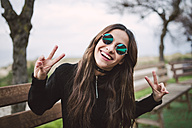 Portrait of young woman wearing mirrored sunglasses showing victory signs - RAEF01714