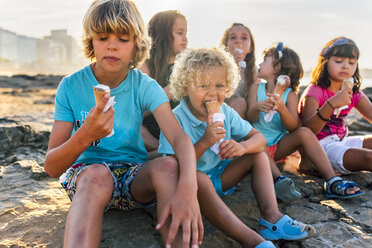 Group of six children eating icecream on the beach - MGOF02819