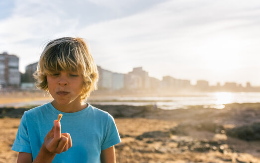 Blond boy eating icecream on the beach at sunset - MGOF02822