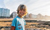 Portrait of smiling blond on the beach at sunset - MGOF02825