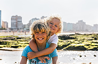Portrait of two happy brothers on the beach - MGOF02829