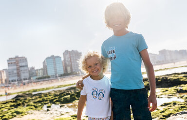 Portrait of two happy brothers on the beach - MGOF02838