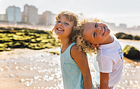 Portrait of happy little boy and girl standing bback to back on the beach - MGOF02841