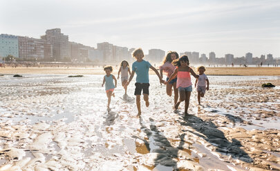 Group of six children running together on the beach - MGOF02847