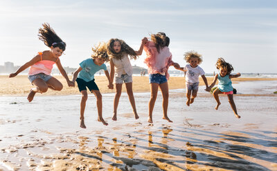 Group of six children jumping in the air on the beach - MGOF02850