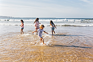 Four children splashing with water at seaside - MGOF02853