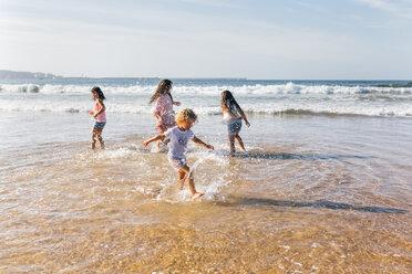 Four children splashing with water at seaside - MGOF02853