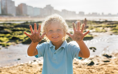 Portrait of smiling little boy showing his sandy hands on the beach - MGOF02856