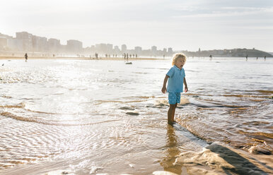 Little boy standing in cold water on the beach - MGOF02859