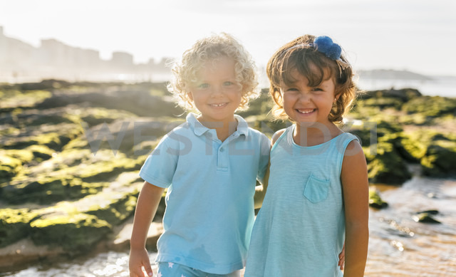 Portrait of happy little boy and girl side by side on the beach - MGOF02862