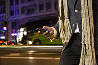 Close-up of man using his cell phone in a street at night - ABZF01812