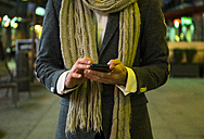 Close-up of man using his cell phone in the city at night - ABZF01818