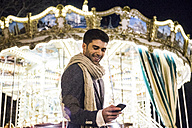 Man using his cell phone at a carousel at night - ABZF01827