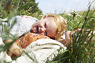 Happy mother and son lying in meadow - FSF00663