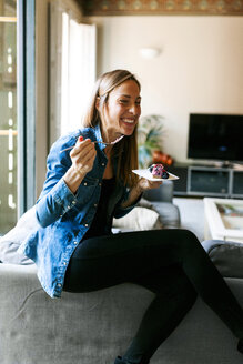 Happy young woman eating a healthy dessert at home - VABF01064