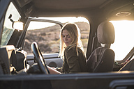 Woman sitting in car at sunset - SIPF01387