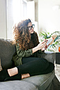 Young woman wearing glasses sitting on couch reading book - VABF01088