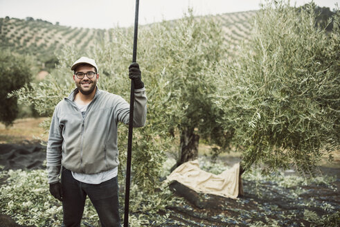 Spain, portrait of smiling worker in olive grove - JASF01478