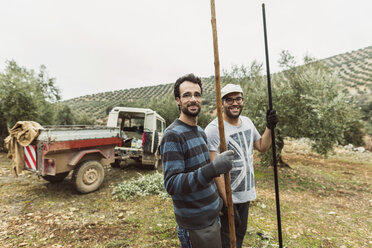 Spain, portrait of two smiling workers with tools in olive grove - JASF01487