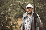 Spain, portrait of smiling worker with wooden stick in olive grove - JASF01499