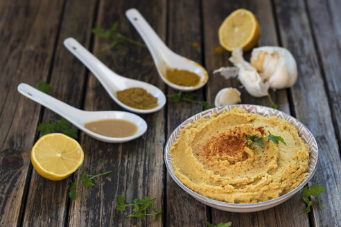 Bowl of Hummus and ingredients on wood - YFF00627
