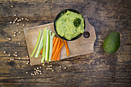 Bowl of avocado hummus, avocado, chick-peas and crudites on wood - LVF05823