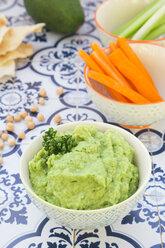 Bowl of avocado hummus, avocado, chick-peas, crudites and flat bread on tiles - LVF05826