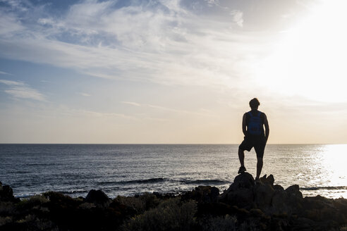 Spain, Tenerife, silhouette of man standing in front of the sea at sunset - SIPF01395