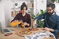 Young couple eating pizza and drinking juice for lunch, laptop standing on table - RTBF00619