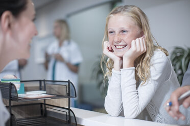 Happy girl standing at hospital reception - ZEF12608