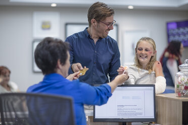 Sick girl getting lollipop from receptionist in hosptal - ZEF12626