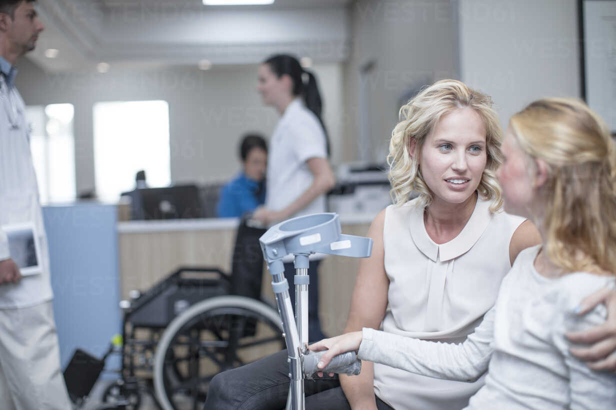 Girl with crutches sitting with her mother in reception area - ZEF12629 - zerocreatives/Westend61