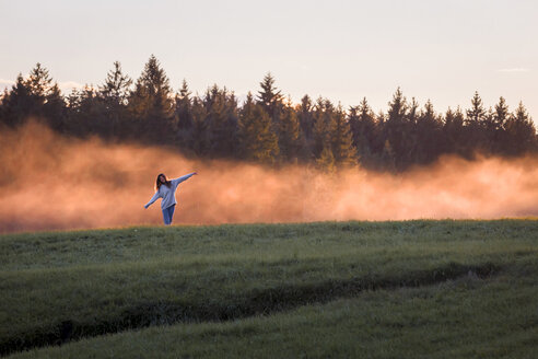Woman with arms outstretched standing in front of haze on a meadow at sunset - WVF00831